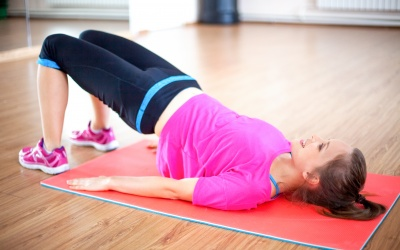 Portrait of happy young Caucasian woman wearing sportswear doing pelvic muscle exercise lying on mat and smiling in gym